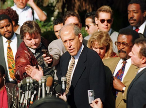 Larry Feldman (talking into microphone) and Johnnie Cochran (in brown jacket) at the press conference announcing the settlement.
